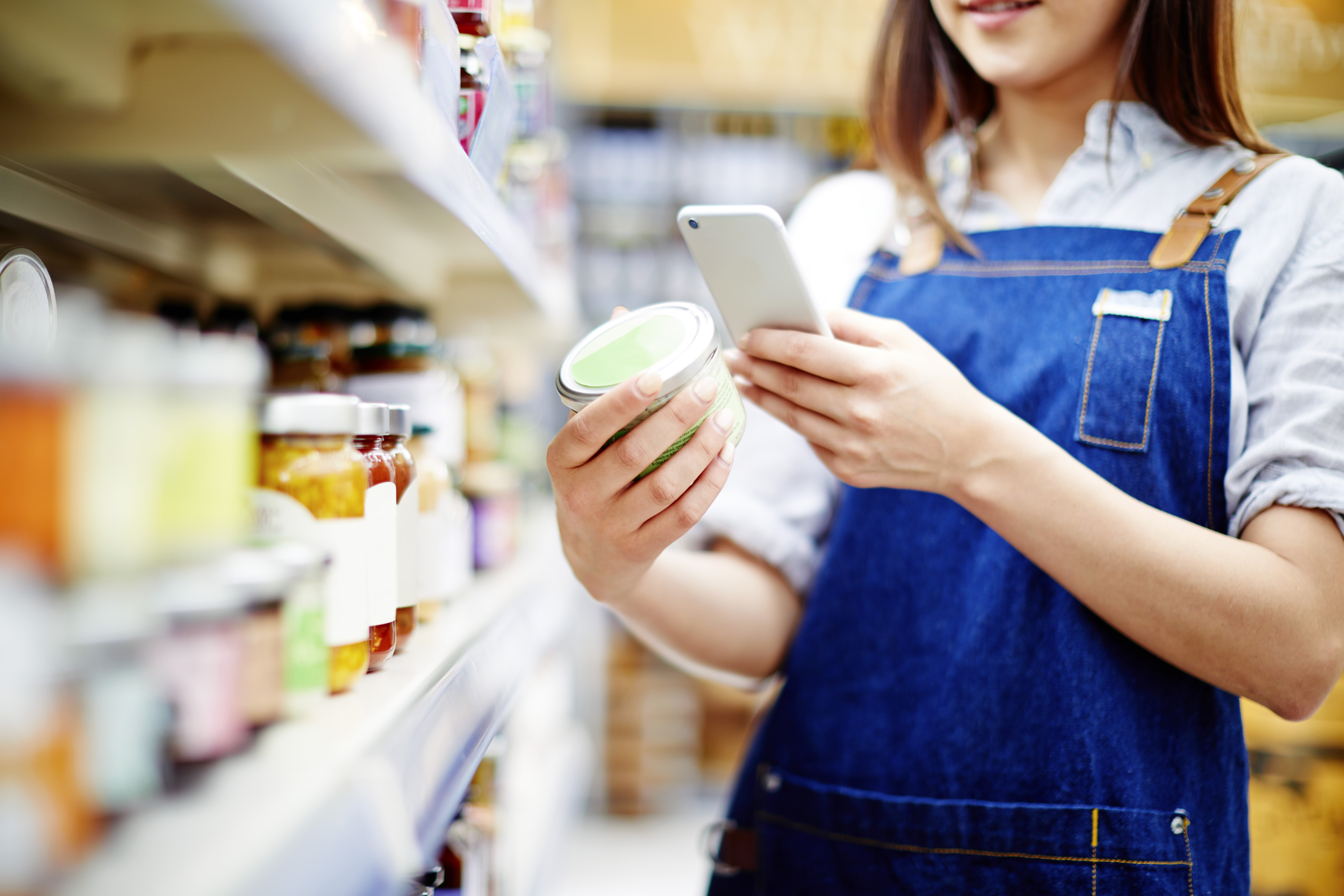 Deli owner scanning label on food container with smart phone